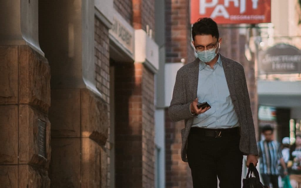 A man in a face mask uses their phone (Image by Kate Trifo)