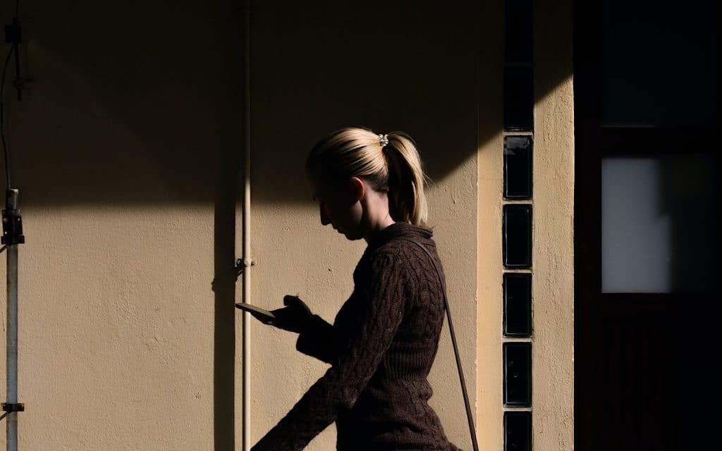 Photo of a woman walking by using their phone