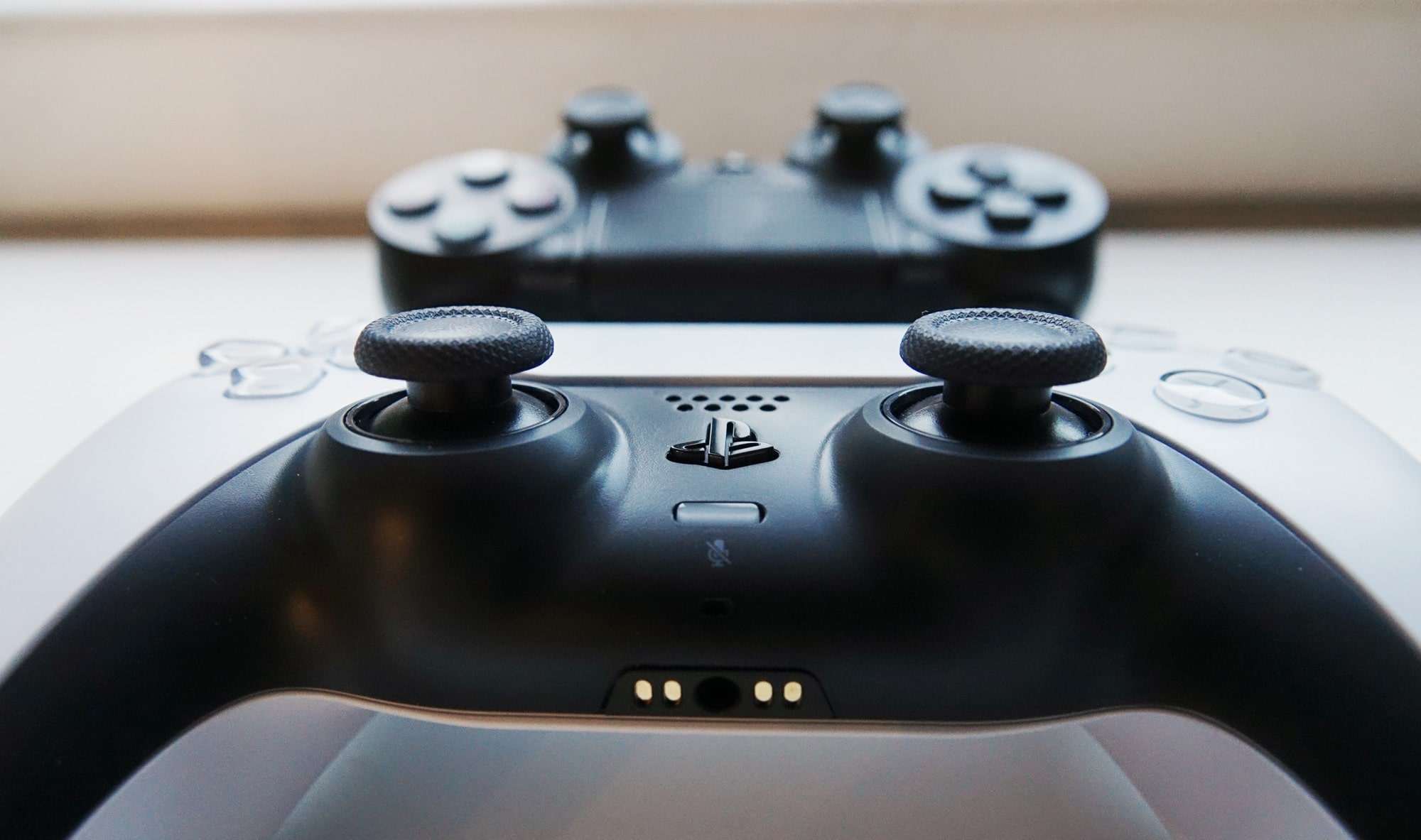 A PS5 controller in front of a PS4 controller