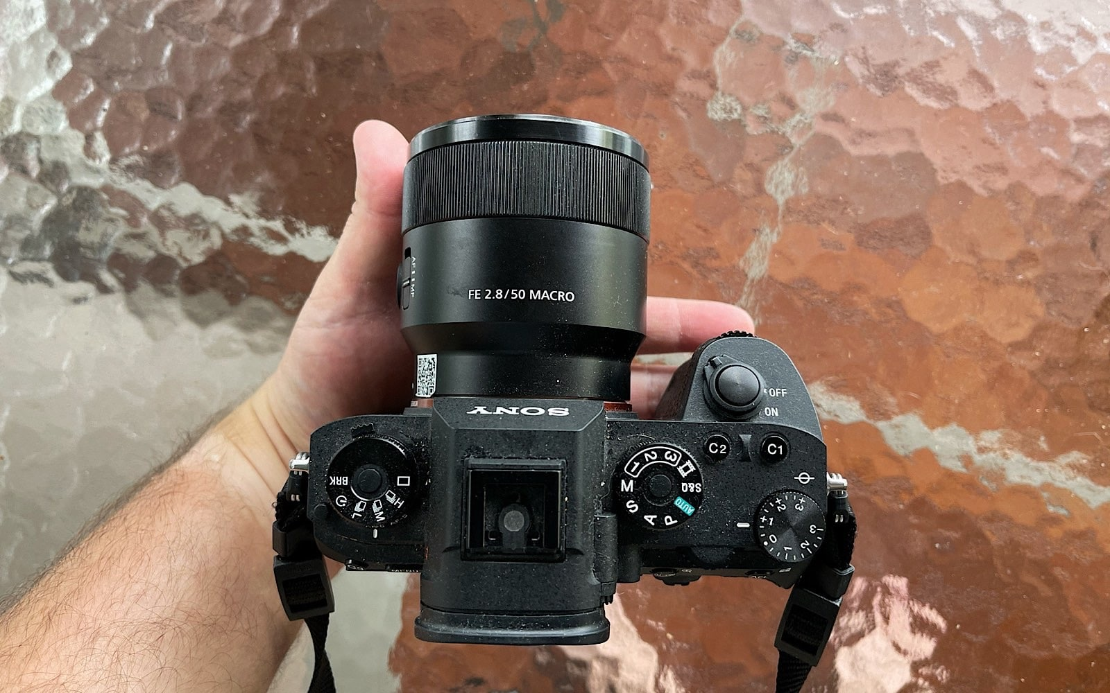 With your palm laying flat, place the camera in it, resting the lens against your thumb and the grip in your fingers. The edge of the camera should line up to the edge of your hand.