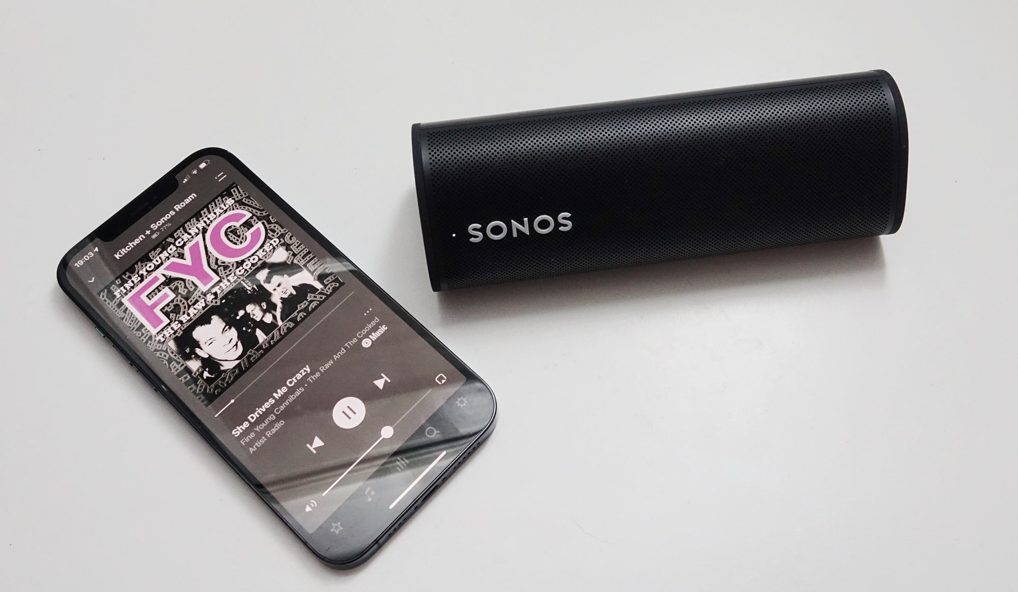 The Sonos Roam next to an iPhone 12 Pro Max.