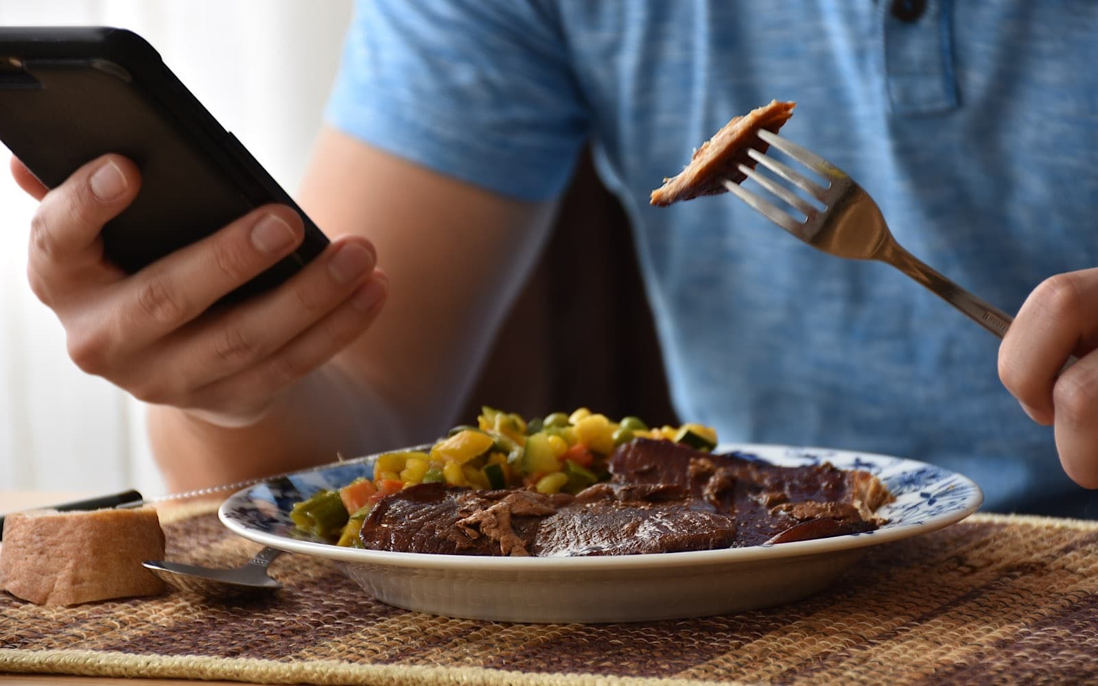 Someone eating a meal while checking their phone