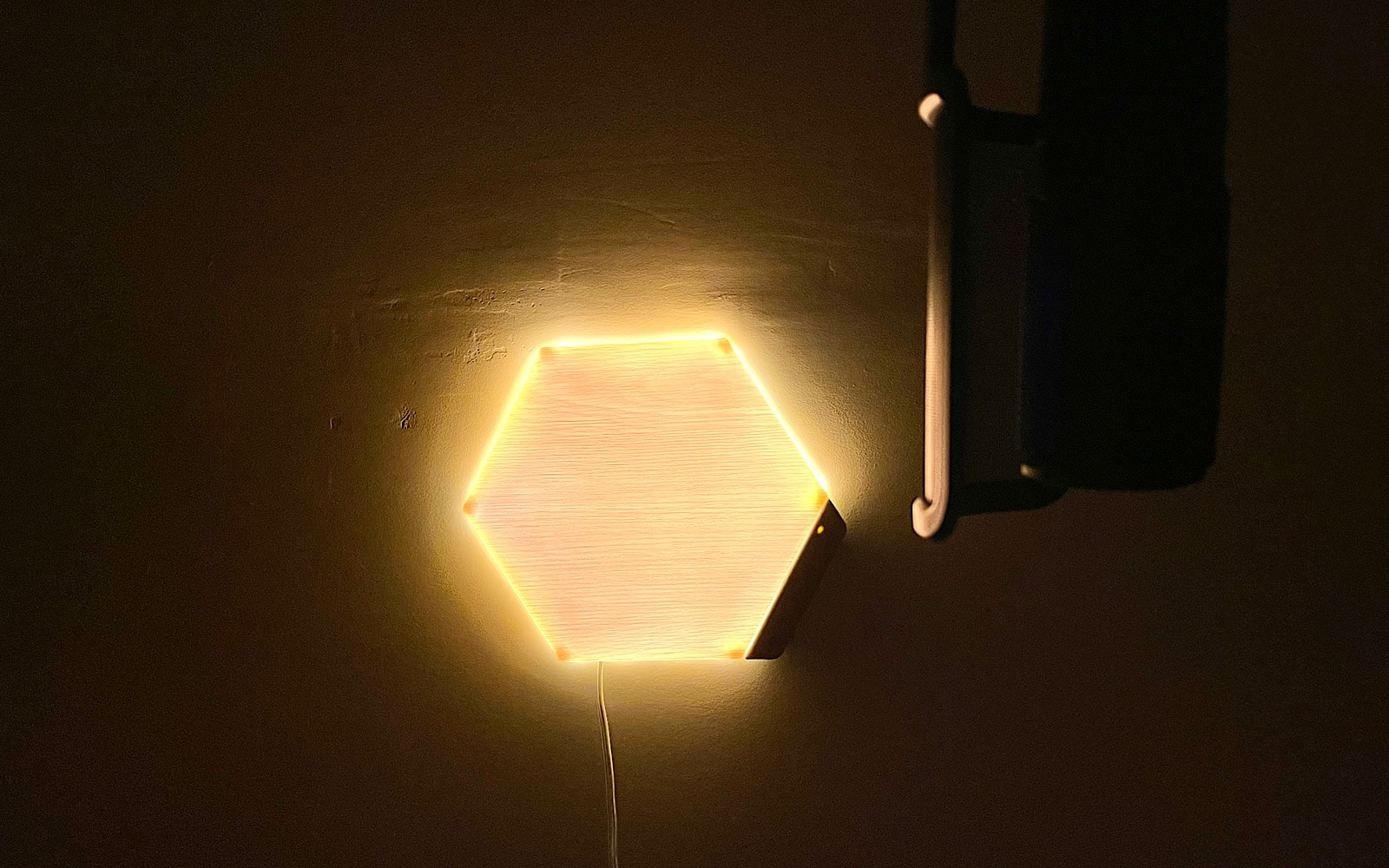 One Nanoleaf Elements module sits in our studio glowing, lighting up the microphone.
