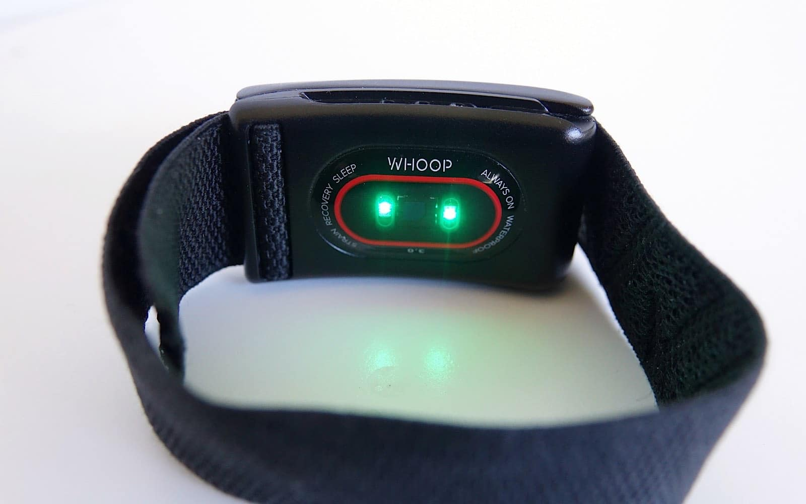 The Whoop 3.0 band shines green lights for heart rate tracking.
